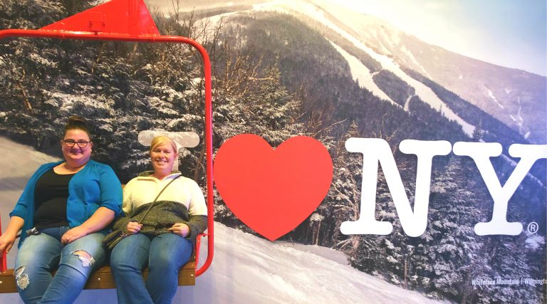 2 girls on a chair lift in front of a I heart NY sign