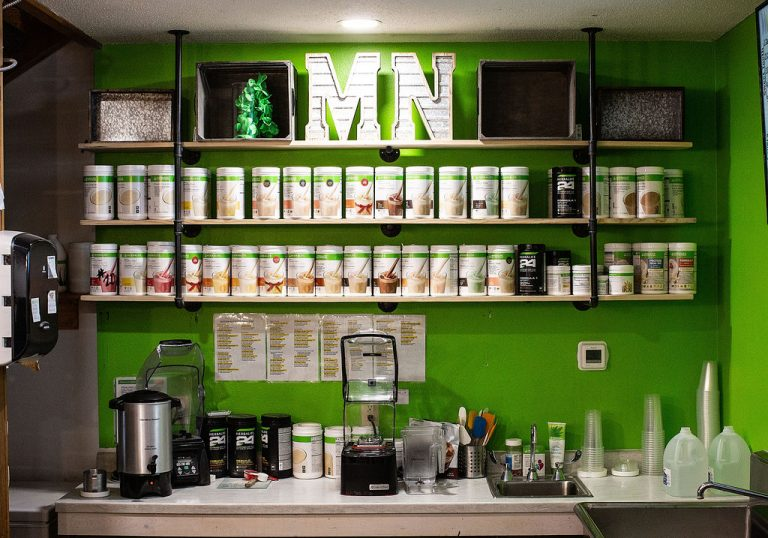 Green wall with Herbalife Shake Canisters lining the wall on shelves