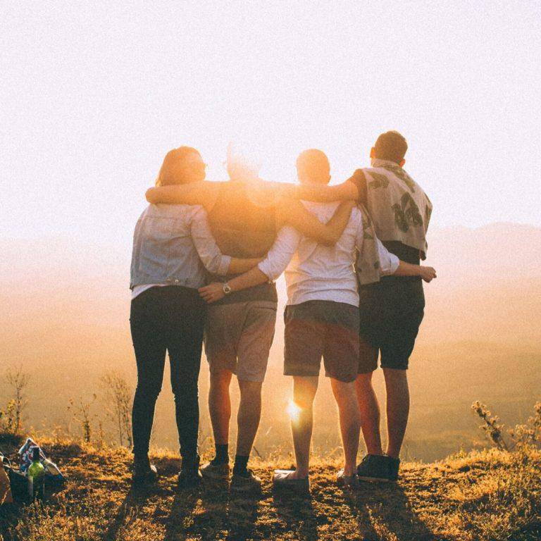 Group of 4 people with their backs to the camera and the sun shining around them