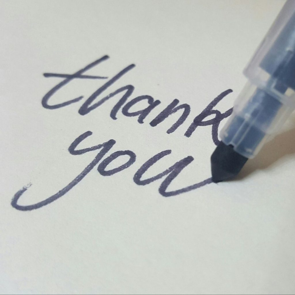 pen writing Thank You on a card
