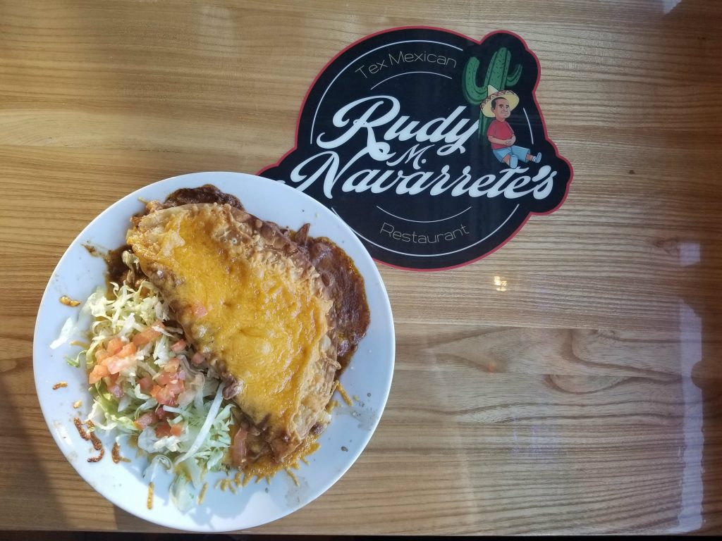 Plate with Food on a Table with the Rudy M. Navarrete's Logo