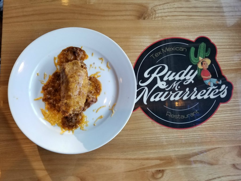 Chicken Mole on a plate on a table with the Rudy M. Navarrete's logo