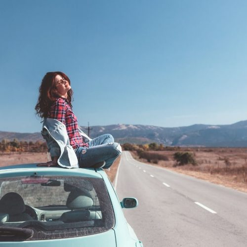 Girl sitting on top of her teal car on the side of the road